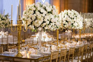 wedding-reception-with-gold-chairs-tall-gold-candleabra-tall-centerpiece-white-flowers