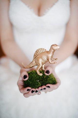 bride-holding-moss-pillow-with-golden-dinosaur-figurine