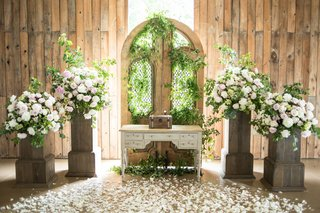 rustic-chic-barn-wedding-ceremony-floral-arrangements-on-wooden-stand-gate-with-greenery