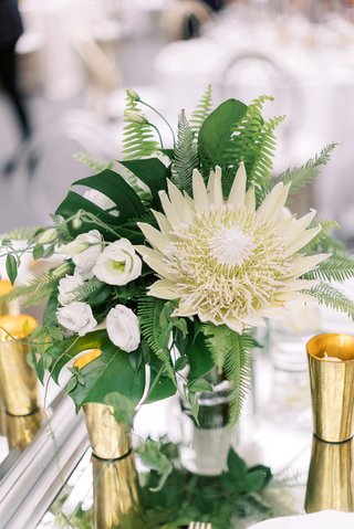 low-wedding-centerpiece-king-protea-white-flower-monstera-leaf-fern-gold-candle-votives-tropical