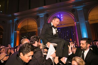 guests-hoisting-up-groom-on-chair-during-hora-at-brooklyn-museum-wedding-purple-lighting