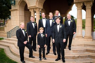 groom-in-tuxedo-with-bow-tie-with-groomsmen-on-steps-of-grand-del-mar