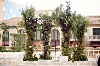 chuppah-with-lush-greenery-and-lavender-and-violet-flowers