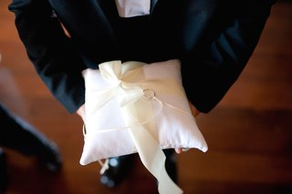 ring-bearer-carrying-wedding-bands-on-plush-pillow