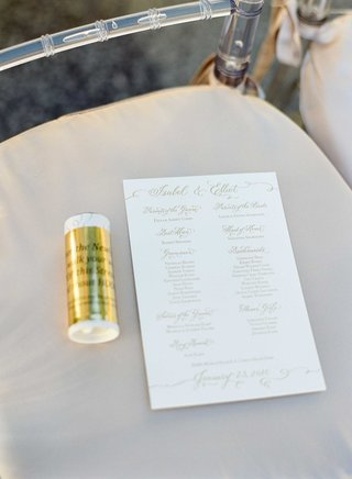 lucite-chair-with-beige-cushion-white-and-gold-ceremony-program-with-list-of-wedding-party-parents