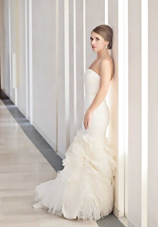 chicago-bride-poses-against-a-white-wall-in-a-fitted-mermaid-wedding-dress-by-vera-wang