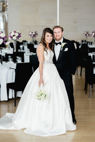 wedding-portrait-in-venue-space-ballroom-wood-floor-black-chairs-purple-white-flowers-wedding-dress