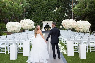 groom-in-lanvin-bride-in-reem-acra-hold-hands-outside-classic-outdoor-ceremony
