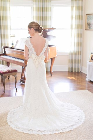 bride-wears-a-lace-watters-dress-with-cap-sleeves-sash-tied-into-a-bow-and-court-length-train