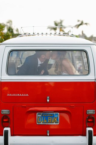 bride-and-groom-kiss-in-back-window-of-1971-volkswagen-red-bus