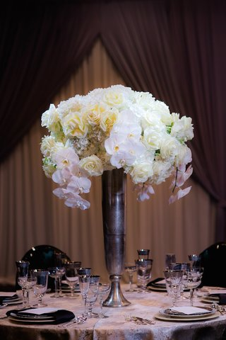 wedding-reception-table-with-a-tall-silver-vase-white-orchids-roses-hydrangeas