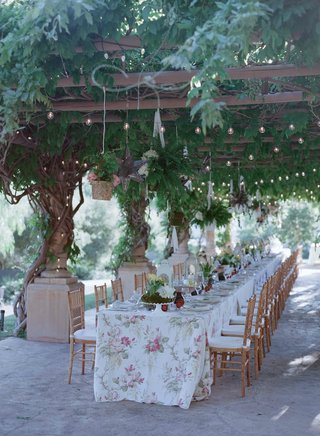 wisteria-canopy-over-long-dinner-table-with-flower-print-linens
