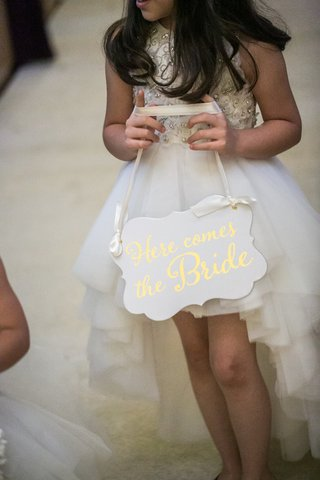 older-flower-girl-in-high-low-dress-carrying-a-here-comes-the-bride-sign