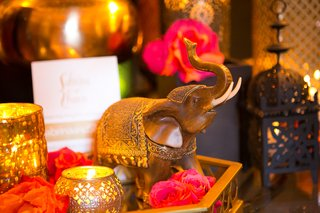 moroccan-themed-engagement-party-with-tray-wood-elephant-pink-orange-roses-gold-votive-candles