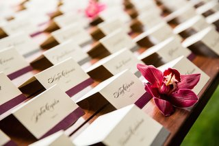 white-escort-cards-with-black-script-and-purple-ribbon-at-bottom