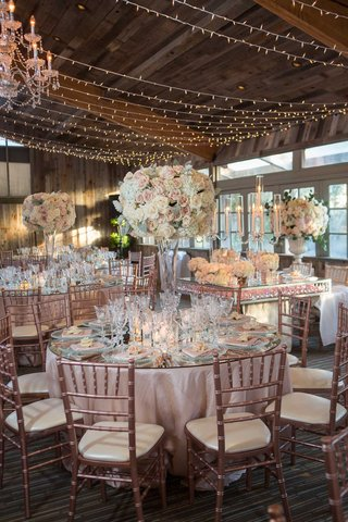 wedding-reception-ballroom-wood-ceiling-beams-string-lights-tall-centerpiece-mirror-table-rose-gold
