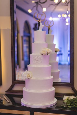 white-six-layer-tier-wedding-cake-with-fresh-flowers-and-classic-cake-topper-in-front-of-mirror