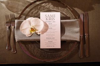 wedding-reception-translucent-charger-plate-silver-rim-with-grey-napkin-simple-menu-and-white-orchid