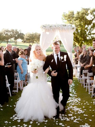 bride-in-eve-of-milady-wedding-dress-holding-hands-with-groom-in-suit-with-flower-petals-in-air-toss