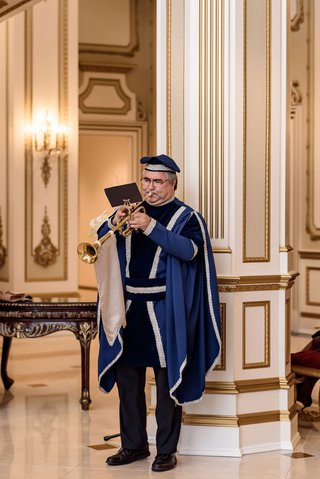 wedding-ceremony-entertainment-man-playing-trumpet-in-royal-wedding-attire-classic-entertainment