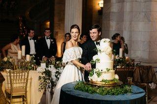 bride-in-lace-off-shoulder-wedding-dress-moms-dress-groom-cutting-classic-wedding-cake-design