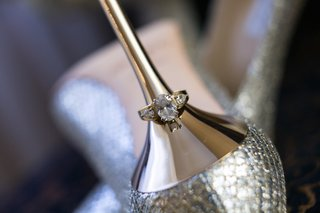 engagement-ring-with-round-center-diamond-pear-side-diamonds-on-jimmy-choo-gold-heel