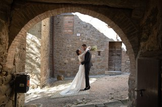 wedding-portrait-in-tuscany-with-bride-and-groom-framed-in-archway
