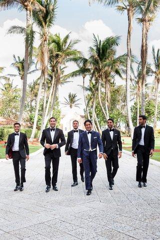 wedding-party-groomsmen-in-tuxedos-groom-in-navy-blue-tuxedo-walking-down-path-in-palm-beach-hotel