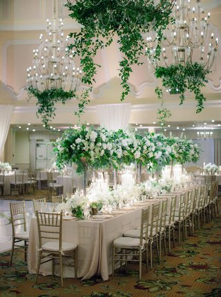 wedding-reception-ballroom-long-table-gold-chair-tall-green-centerpiece-white-flowers-chandeliers