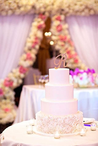 four-tier-wedding-cake-with-rose-frosted-details-on-base-glitter-gold-monogram-cake-topper