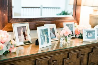 wedding-reception-credenza-buffet-table-with-family-photos-in-frames-mirror-pink-flowers-lamps
