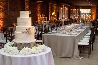 wedding-cake-with-four-layers-fresh-roses-flowers-pink-ivory-champagne-brick-wall-venue-silver-linen