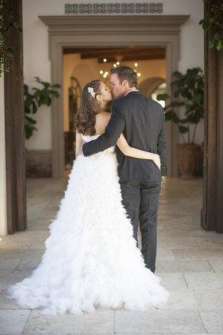 bride-in-monique-lhuillier-wedding-dress-curled-hair-headpiece-kisses-groom-hugs-from-back