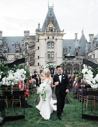 bride-in-strapless-mermaid-gown-and-groom-in-tuxedo-bouquet-walking-up-aisle-through-gates-chateau