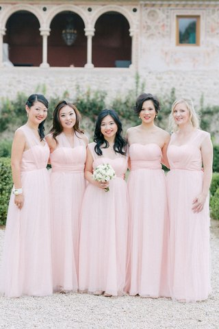 bridesmaids-in-light-pink-long-dresses-illusion-necklines-maid-of-honor-holding-bouquet