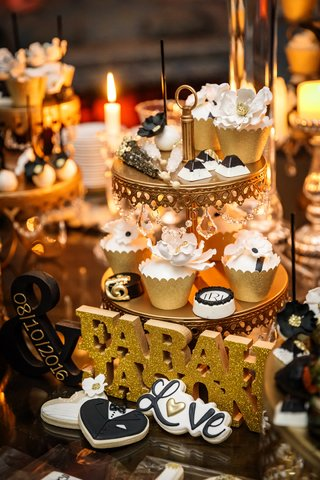 dessert-table-with-small-desserts-on-tiers-of-cake-stand-bride-and-grooms-names-with-wedding-date