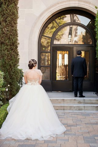 back-of-bride-in-lazaro-wedding-dress-waiting-for-groom-during-first-look-at-wedding