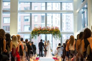daytime-wedding-in-new-york-city-hotel-lucite-columns-and-flowers-foliage-floating-above-couple
