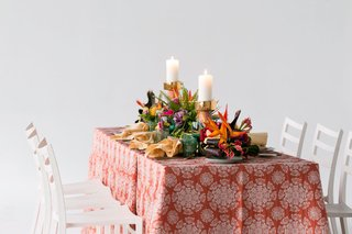 wedding-reception-styled-shoot-white-chairs-orange-linen-pattern-bird-of-paradise-palm-green