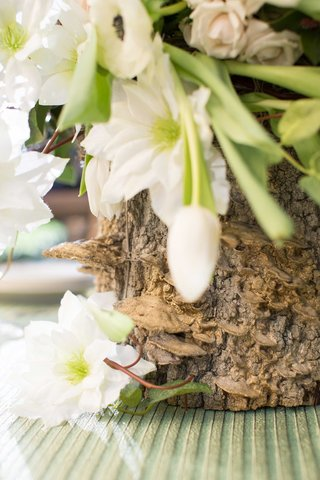 tree-trunk-vase-with-green-and-white-flowers-floral-arrangement-green-table-linens