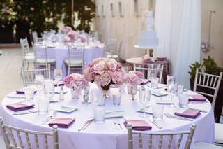 rooftop-wedding-reception-tables-with-purple-linens-roses-silver-chairs