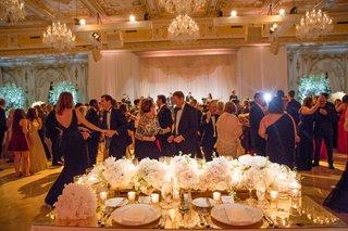 wedding-reception-guests-on-dance-floor-view-from-bride-and-groom-seats-in-ballroom-chandeliers