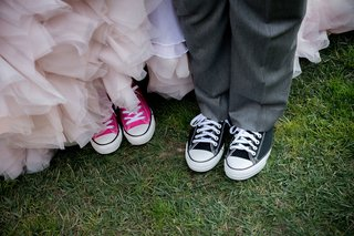 bride-in-blush-ruffle-wedding-dress-with-pink-converse-and-groom-in-grey-suit-black-converse