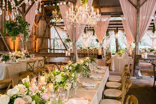 barn-wedding-venue-blush-drapes-low-centerpieces-long-tables-wood-chairs-chandeliers
