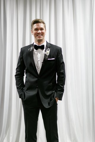 groom-in-classic-black-tuxedo-hands-in-pockets-white-feather-boutonniere-white-drapery
