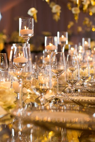 glowing-reception-table-with-floating-candles-in-glasses-among-wine-glasses