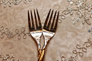 bride-and-grooms-cake-forks-inscribed-with-i-do-and-me-too-on-tablecloth-with-silver-embroidery