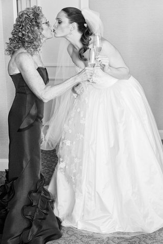black-and-white-photo-of-bride-in-ball-gown-kissing-mother-of-bride-in-strapless-gown-champagne