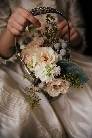 flower-girl-holding-small-basket-antique-looking-with-pink-white-flowers-and-silver-brunia-berries