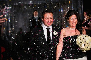 a-newlywed-groom-in-a-black-tuxedo-and-bride-in-a-black-and-white-gown-walk-through-confetti